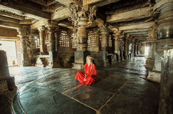 Young woman in traditional indian red dress sitting on stone floor of 12th century temple Hoysaleswara, India. Meditation time Stock Image