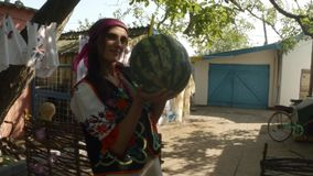 A young woman in a traditional Ukrainian folk costume holds a large watermelon in her hands in a rural yard. Collection, a girl in a traditional Ukrainian folk stock video