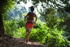 Woman trail runner running on tropical forest trail. Young woman trail runner running on tropical forest trail stock images