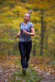 Young woman trail running in the forest Royalty Free Stock Photos
