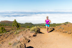 Young woman trail running in mountains Stock Photo