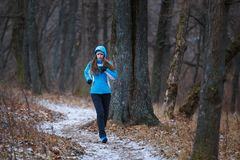 Young woman on trail running in winter park.  Royalty Free Stock Photo