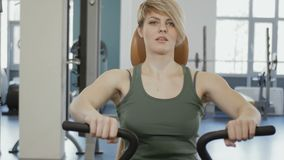 Young woman train her back at training apparatus. The camera moves from the left to right. Young woman wearing sporty outfit is in the gym. Sporty young smiling stock footage