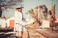 Young woman on train station reading map royalty free stock image