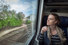 The young woman is on the train and watches through the window o Royalty Free Stock Photo