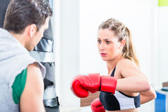 Young woman with trainer in boxing sparring Stock Photo