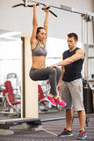 Young woman with trainer doing leg raises in gym Royalty Free Stock Photos