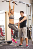 Young woman with trainer doing leg raises in gym Stock Image