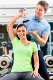 Young woman and trainer at exercise in gym Stock Image