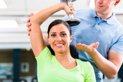 Young woman and trainer at exercise in gym Stock Images