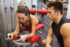 Young woman with trainer exercising on gym machine Royalty Free Stock Photos