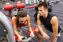Young woman with trainer exercising on gym machine Royalty Free Stock Image
