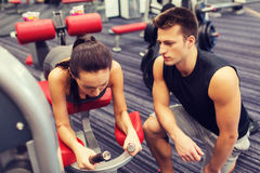 Young woman with trainer exercising on gym machine Royalty Free Stock Photography