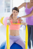 Young woman with trainer holding resistance band Stock Photography