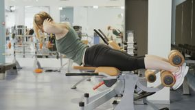 Young woman training back on the training apparatus in gym. Young woman wearing sporty outfit is in the gym. Sporty young woman lies at the training apparatus stock video footage