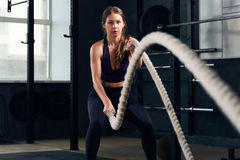 Young Woman Training with Battle Ropes royalty free stock images
