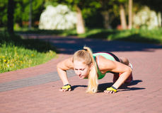 Young woman training in city park at summer day Stock Photos