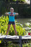 Young woman training with dumbbells on wooden bridge and water Royalty Free Stock Photo