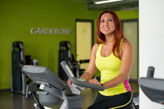 Young woman training on an exercise bike Royalty Free Stock Images