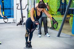 Young woman training exercise push ups with trx Royalty Free Stock Photography