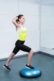 Young woman training at fitness club. Photo of beautiful young sporty woman. Fitness girl working out with bosu at fitness club Royalty Free Stock Photography