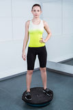 Young woman training at fitness club. Photo of beautiful young sporty woman. Fitness girl working out with bosu at fitness club. Woman looking at camera Stock Photo