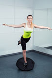 Young woman training at fitness club. Photo of beautiful young sporty woman. Fitness girl working out with bosu at fitness club. Woman smiling and looking at Stock Photos