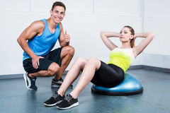 Young woman training at fitness club. Photo of beautiful young sporty woman. Fitness girl working out with bosu at fitness club. Trainer helping woman Royalty Free Stock Image