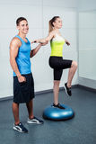 Young woman training at fitness club. Photo of beautiful young sporty woman. Fitness girl working out with bosu at fitness club. Trainer helping woman Stock Photos