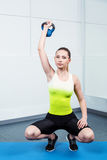 Young woman training at fitness club. Photo of beautiful young sporty woman. Girl working out with kettlebell. Woman looking at camera Royalty Free Stock Photos