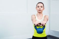 Young woman training at fitness club. Photo of beautiful young sporty woman. Girl working out with kettlebell. Woman looking at camera Stock Images