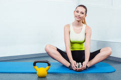 Young woman training at fitness club. Photo of beautiful young sporty woman. Girl working out with kettlebell. Woman looking at camera and smiling Stock Photography