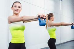 Young woman training at fitness club. Photo of beautiful young sporty woman. Girl working out with kettlebell. Woman looking at camera and smiling Royalty Free Stock Photo
