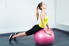Young woman training at fitness club. Photo of beautiful young sporty woman. Girl working out with pink fitness ball Royalty Free Stock Photography