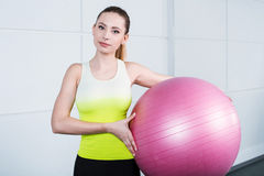 Young woman training at fitness club. Photo of beautiful young sporty woman. Girl working out with pink fitness ball. Woman looking at camera Stock Photography
