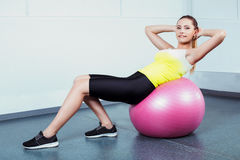 Young woman training at fitness club. Photo of beautiful young sporty woman. Girl working out with pink fitness ball. Woman looking at camera and smiling Stock Image