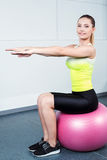 Young woman training at fitness club. Photo of beautiful young sporty woman. Girl working out with pink fitness ball. Woman looking at camera and smiling Stock Photos