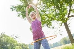 Young woman training with fitness hoop. In summer at park Stock Image