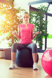 Young woman training in gym with dumbbells in front of a mirror sitting on fitball Royalty Free Stock Photography