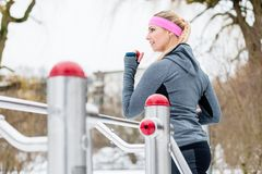 Young woman training her legs on fitness path on winter day. Young woman training her legs on fitness path at winter day in the park Royalty Free Stock Photo