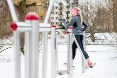 Young woman training her legs on fitness path on winter day. Young woman training her legs on fitness path at winter day in the park Stock Image