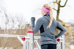 Young woman training her legs on fitness path on winter day. Young woman training her legs on fitness path at winter day in the park Royalty Free Stock Image