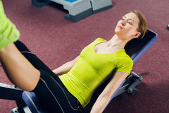 Young woman training her legs at machine press in the gym. stock photo