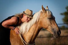 Young woman training horse outside in summer Stock Photo