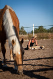 Young woman training horse outside in summer Royalty Free Stock Image