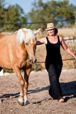 Young woman training horse outside in summer Royalty Free Stock Images