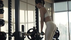 Young woman training incline with fitness equipment front of mirror on gym club. Sports woman training inclination with heavy barbell front of mirror in fitness stock video footage