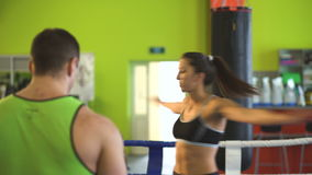 Young woman training pre-match warm-up in the boxing ring with het trainer. stock footage