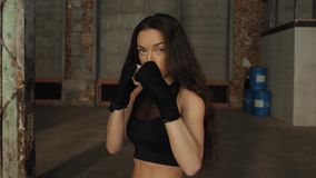 Young woman training portrait punch boxing gloves for punching. Girl making Strong kick. CrossFit. Female boxer woman. Young woman training punch boxing gloves stock video footage