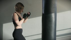 Young woman training punching bag in fitness studio stock footage